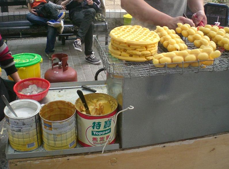 a stall selling puff waffles, cooking equipment, waffle batter, LPG tank, tub, people seating on the bench